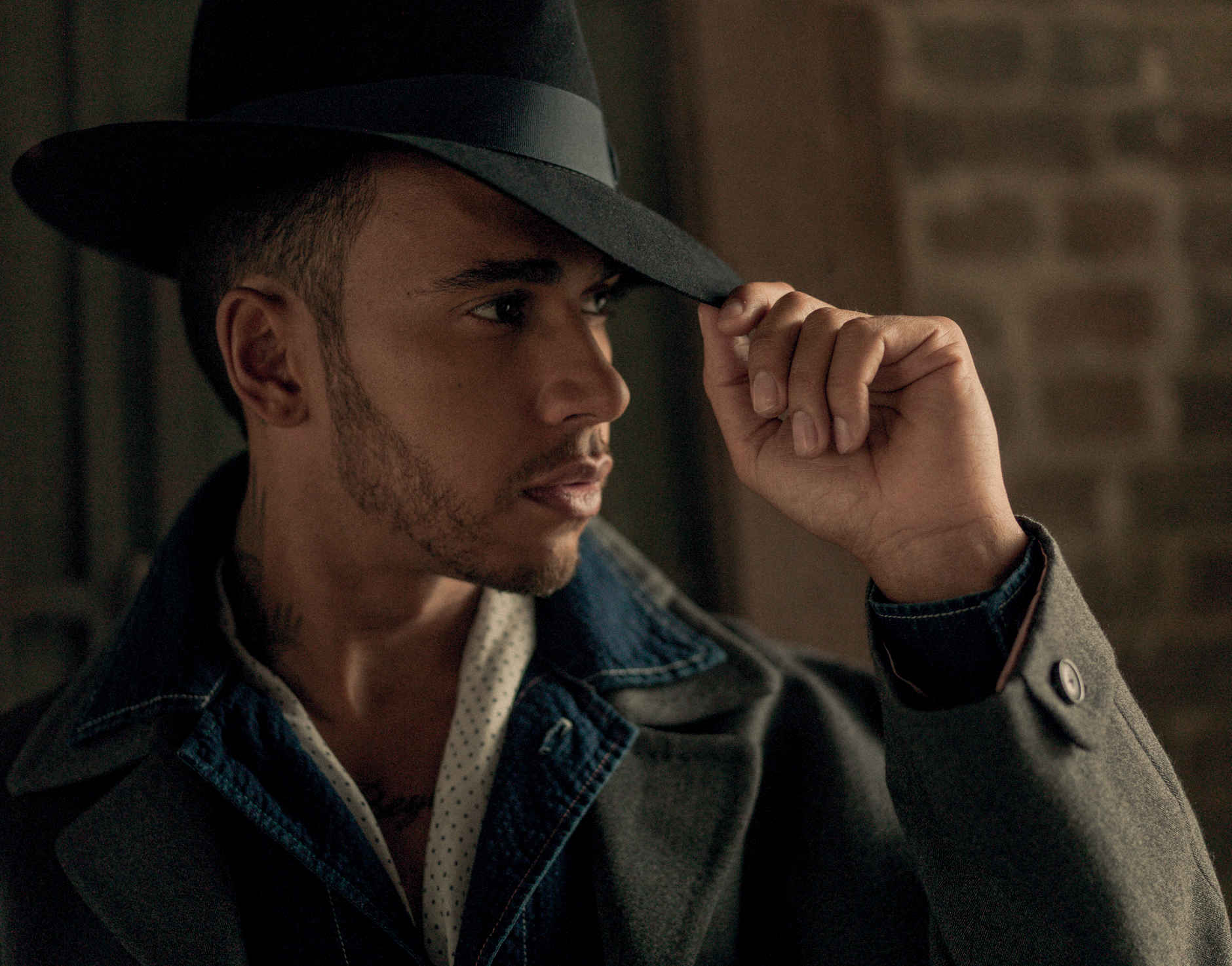 Lewis wears coat and denim shirt, Paul Smith, hat by Dunhill, scarf stylists own